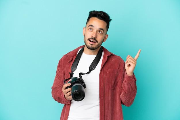 Jovem fotógrafo homem caucasiano isolado em um fundo azul pensando uma ideia apontando o dedo para cima