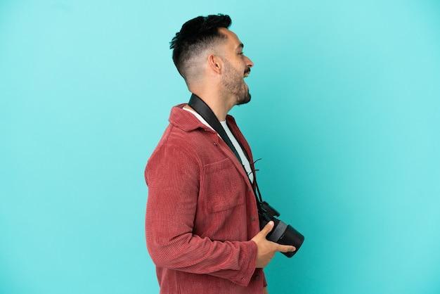 Jovem fotógrafo homem caucasiano isolado em um fundo azul rindo em posição lateral