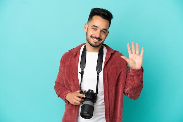 Jovem fotógrafo, homem caucasiano, isolado em um fundo azul, saudando com a mão e com uma expressão feliz.