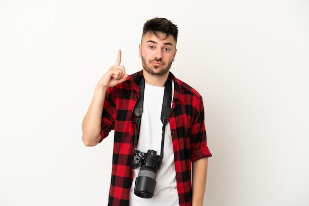 Jovem fotógrafo homem caucasiano isolado no fundo branco apontando com o dedo indicador uma ótima ideia