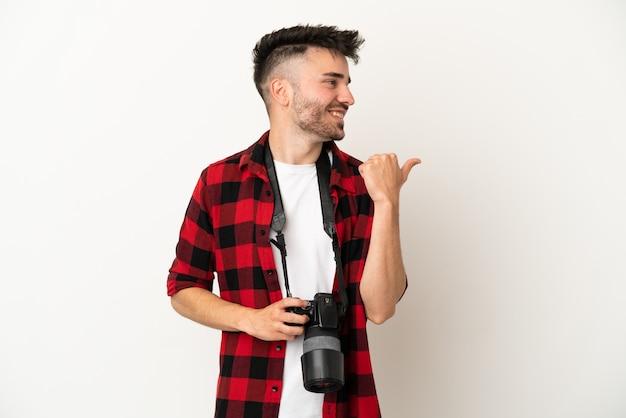 Jovem fotógrafo homem caucasiano isolado no fundo branco apontando para o lado para apresentar um produto