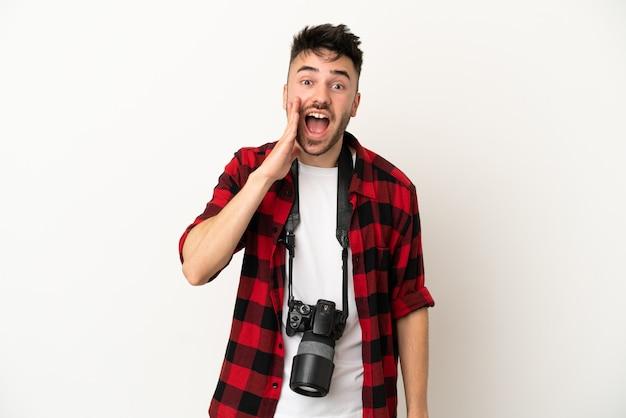 Jovem fotógrafo homem caucasiano isolado no fundo branco com expressão facial de surpresa e choque