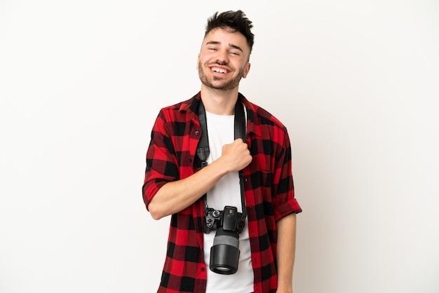 Jovem fotógrafo homem caucasiano isolado no fundo branco comemorando vitória