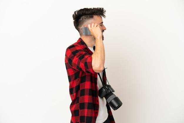 Jovem fotógrafo homem caucasiano isolado no fundo branco, conversando com alguém ao telefone celular