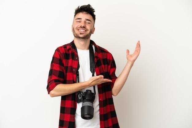 Jovem fotógrafo homem caucasiano isolado no fundo branco, estendendo as mãos para o lado para convidar para vir