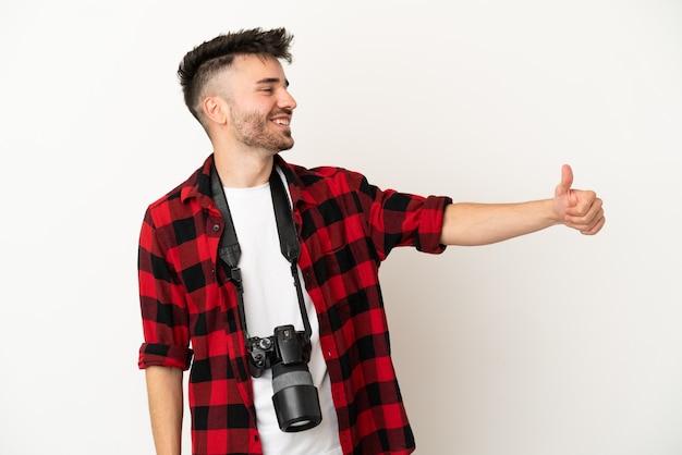 Jovem fotógrafo homem caucasiano isolado no fundo branco fazendo um gesto de polegar para cima