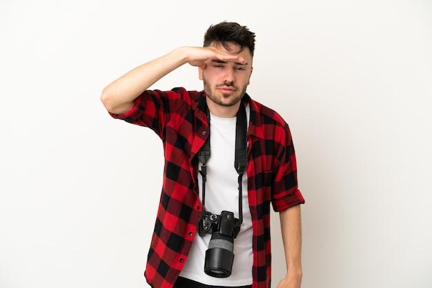 Jovem fotógrafo homem caucasiano isolado no fundo branco olhando para longe com a mão para olhar algo