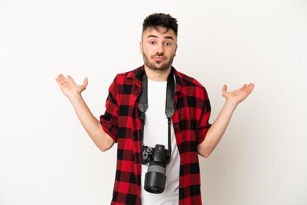 Jovem fotógrafo homem caucasiano isolado no fundo branco tendo dúvidas ao levantar as mãos