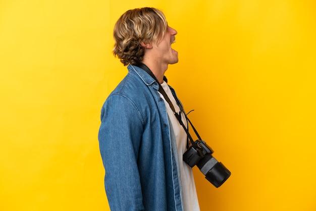 Jovem fotógrafo isolado em um fundo amarelo rindo em posição lateral