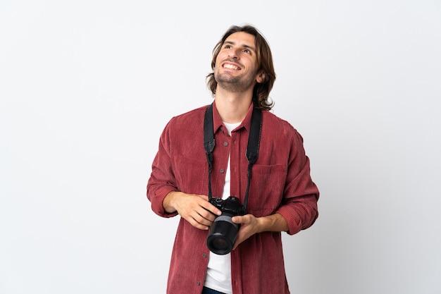Jovem fotógrafo isolado no branco pensando em uma ideia enquanto olha para cima
