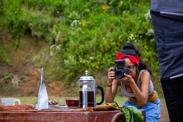 Jovem fotógrafo latino-americano fotografando café nas montanhas da selva peruana