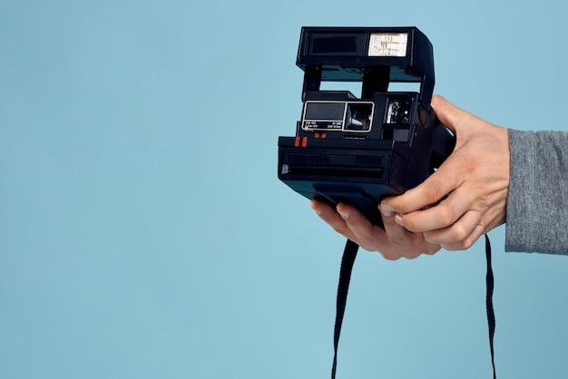 Jovem fotógrafo masculino com uma câmera velha em uma parede azul clara posando emocionalmente