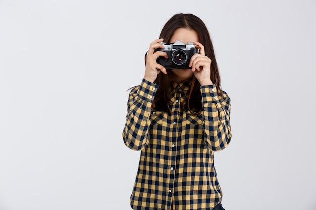 Jovem fotógrafo moreno lindo muro branco.