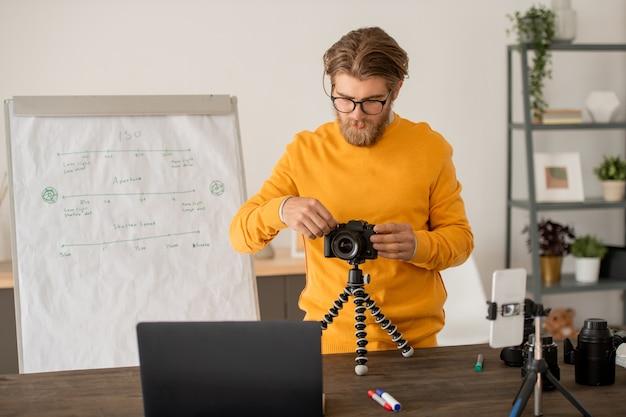 Jovem fotógrafo ou professor de fotografia colocando uma câmera fotográfica profissional na frente do smartphone e laptop durante a aula online