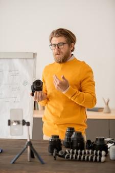 Jovem fotógrafo profissional contemporâneo segurando uma câmera fotográfica e explicando como ela funciona para seu público on-line na aula