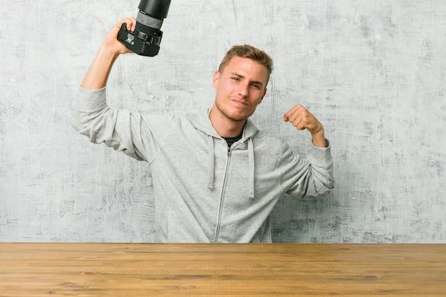 Jovem fotógrafo segurando uma câmera em uma mesa, mostrando o gesto de força com os braços, símbolo do poder feminino