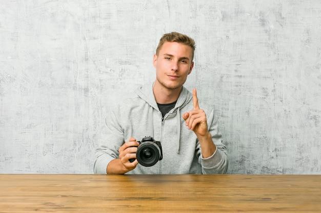 Jovem fotógrafo segurando uma câmera em uma mesa, mostrando o número um com o dedo.
