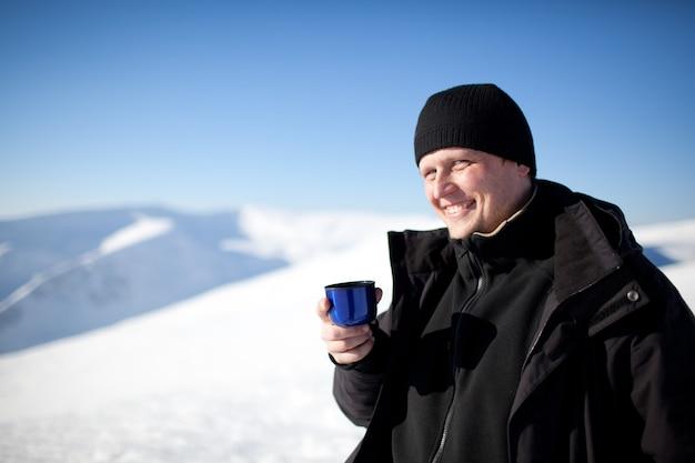 Jovem fotógrafo sorridente com roupas de inverno, bebendo chá da garrafa térmica e sorrindo ao sol