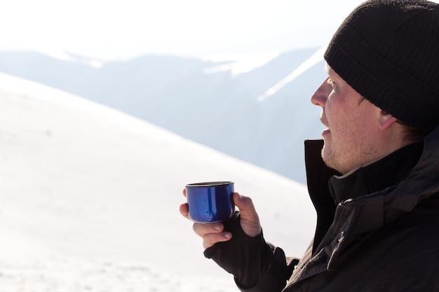 Jovem fotógrafo sorridente com roupas de inverno, bebendo chá da garrafa térmica e sorrindo sob a luz do sol com fundo branco de neve