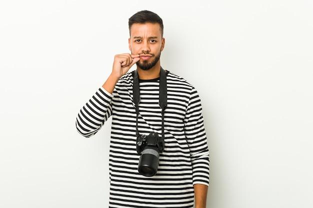 Jovem fotógrafo sul-asiático com os dedos nos lábios, mantendo um segredo.