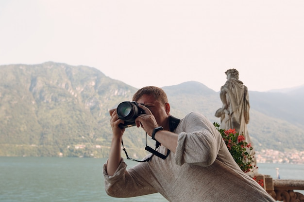 Jovem fotógrafo tira fotos com uma câmera profissional, montanhas e um lago. foto conceito de viagens.