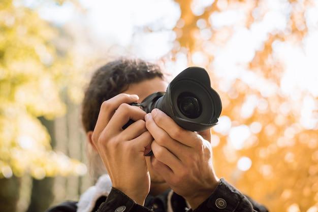 Jovem fotógrafo tirando fotos da natureza no parque da cidade