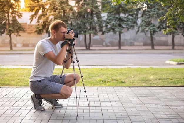 Jovem fotógrafo tirando fotos no parque
