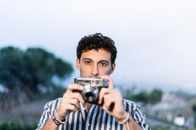 Jovem fotógrafo tirando uma foto com uma câmera retro