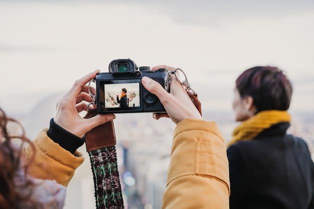 Jovem fotógrafo tirando uma foto de mulher bonita ao ar livre. fotografia, viagem