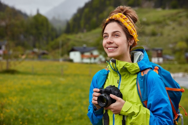Jovem fotógrafo turístico profissional olha para longe, captura belas paisagens