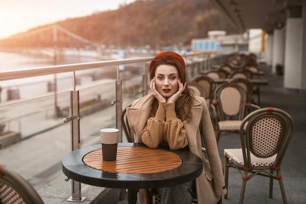 Jovem francesa decepcionada ou frustrada sentada ao ar livre no terraço do restaurante com uma caneca de café