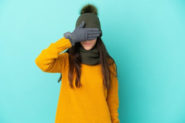 Jovem francesa isolada em um fundo azul com chapéu de inverno cobrindo os olhos com as mãos. não quero ver nada