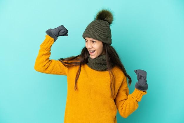Jovem francesa isolada em um fundo azul com chapéu de inverno comemorando uma vitória