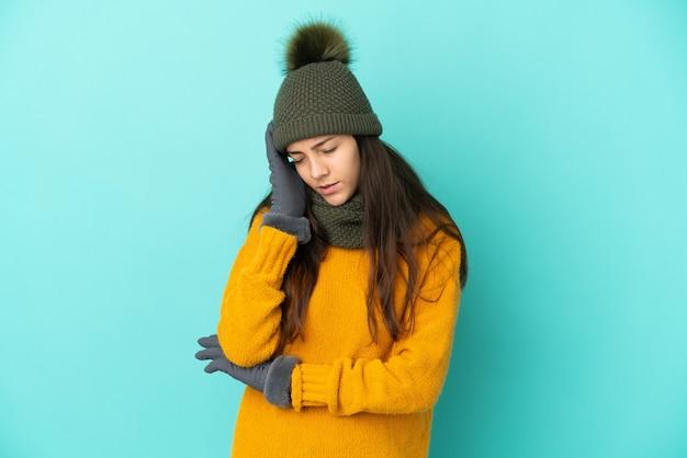 Jovem francesa isolada em um fundo azul com chapéu de inverno e dor de cabeça