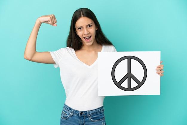 Jovem francesa isolada em um fundo azul segurando um cartaz com o símbolo da paz e fazendo um gesto forte