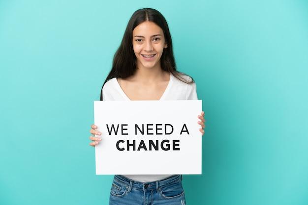 Jovem francesa isolada em um fundo azul segurando um cartaz com o texto precisamos de uma mudança com expressão feliz