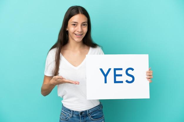Jovem francesa isolada em um fundo azul segurando um cartaz com o texto sim e apontando-o