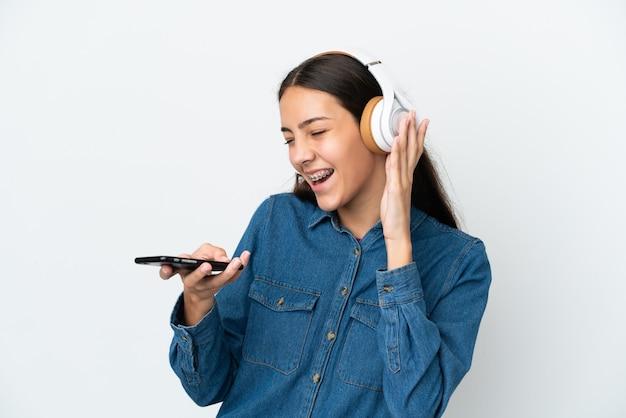 Jovem francesa isolada em um fundo branco ouvindo música com um celular e cantando