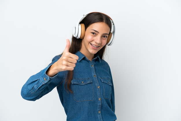 Jovem francesa isolada em um fundo branco ouvindo música e com o polegar para cima