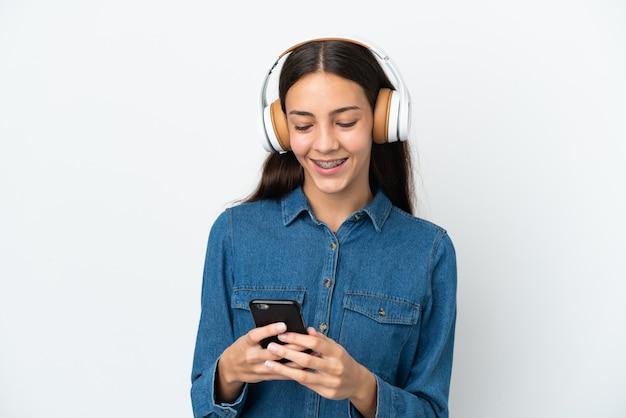 Jovem francesa isolada em um fundo branco ouvindo música e olhando para o celular