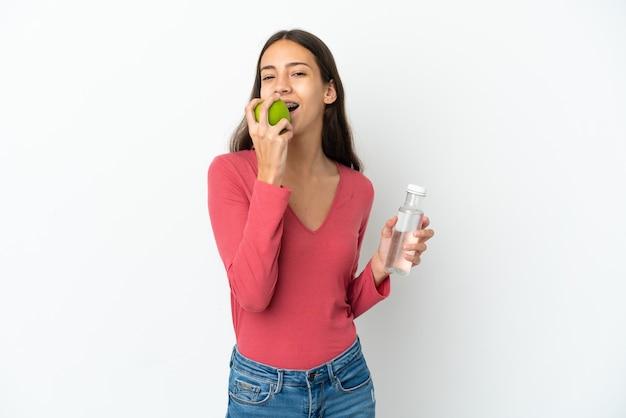Jovem francesa isolada no fundo branco com uma garrafa de água e comendo uma maçã