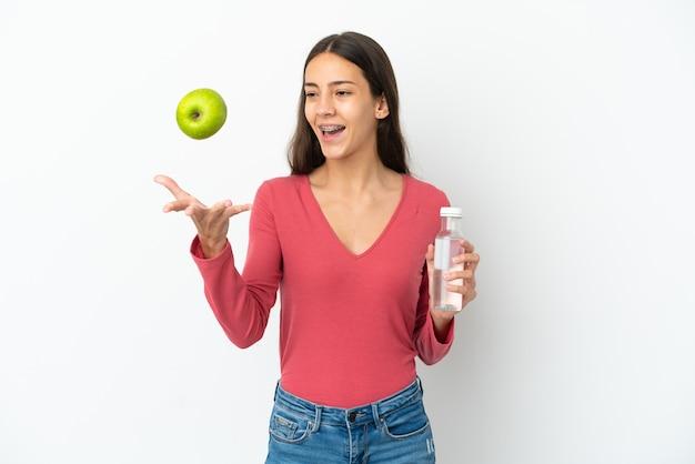 Jovem francesa isolada no fundo branco com uma maçã e uma garrafa de água