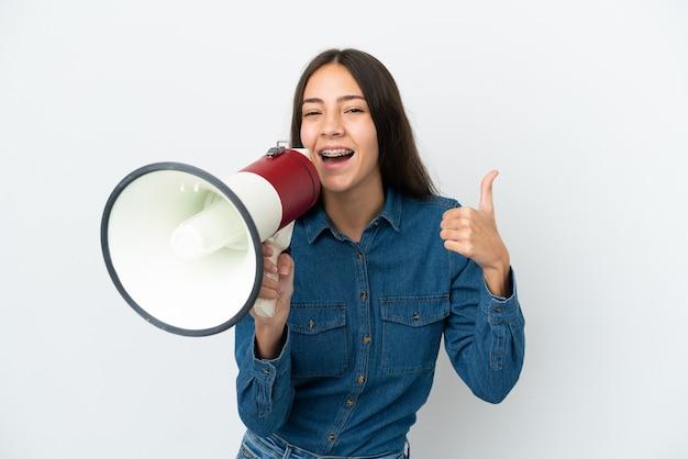 Jovem francesa isolada no fundo branco gritando em um megafone para anunciar algo e com o polegar para cima