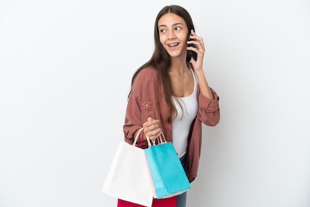 Jovem francesa isolada no fundo branco segurando sacolas de compras e ligando para um amigo com o celular