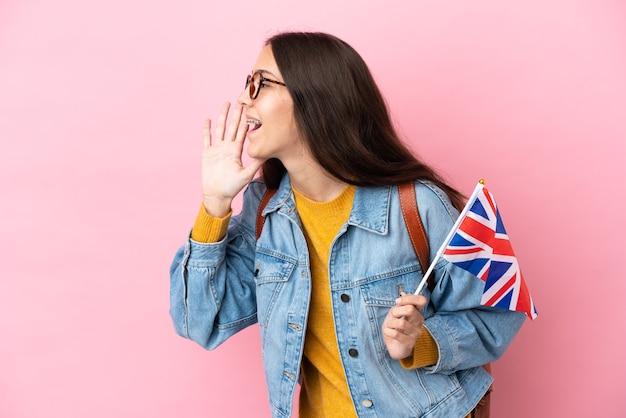 Jovem francesa segurando uma bandeira do reino unido isolada em um fundo rosa gritando com a boca bem aberta para o lado