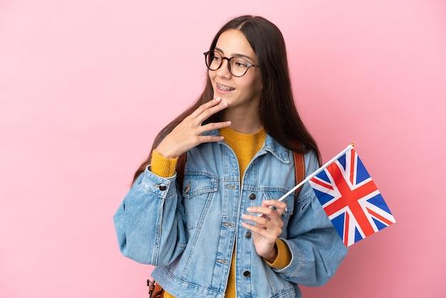 Jovem francesa segurando uma bandeira do reino unido isolada em um fundo rosa, olhando para cima enquanto sorri