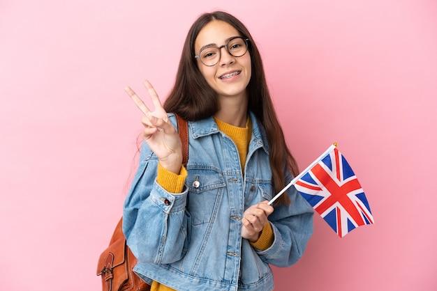 Jovem francesa segurando uma bandeira do reino unido isolada em um fundo rosa, sorrindo e mostrando o sinal da vitória