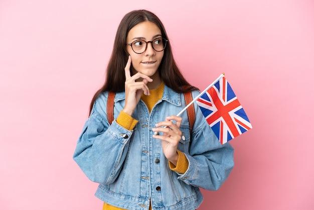 Jovem francesa segurando uma bandeira do reino unido isolada em um fundo rosa, tendo dúvidas e pensando