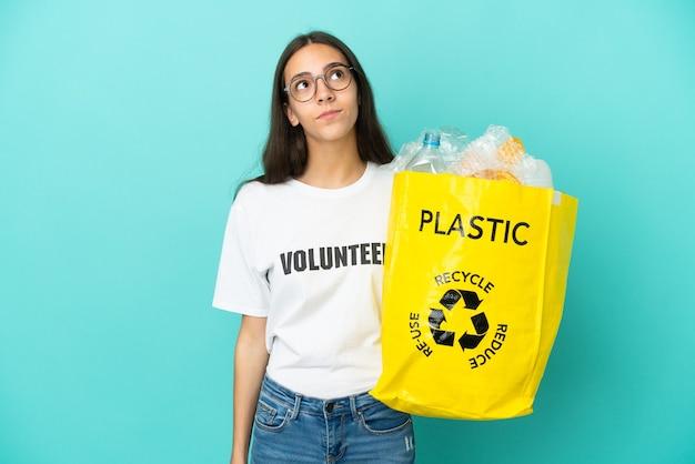 Jovem francesa segurando uma sacola cheia de garrafas de plástico para reciclar e olhando para cima