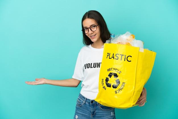 Jovem francesa segurando uma sacola cheia de garrafas de plástico para reciclar, estendendo as mãos para o lado para convidá-la a vir